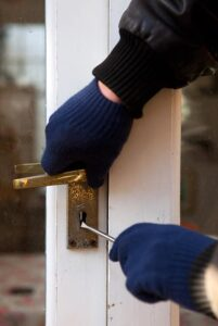 Thief using a screwdriver to break a lock to gain access and rob property.